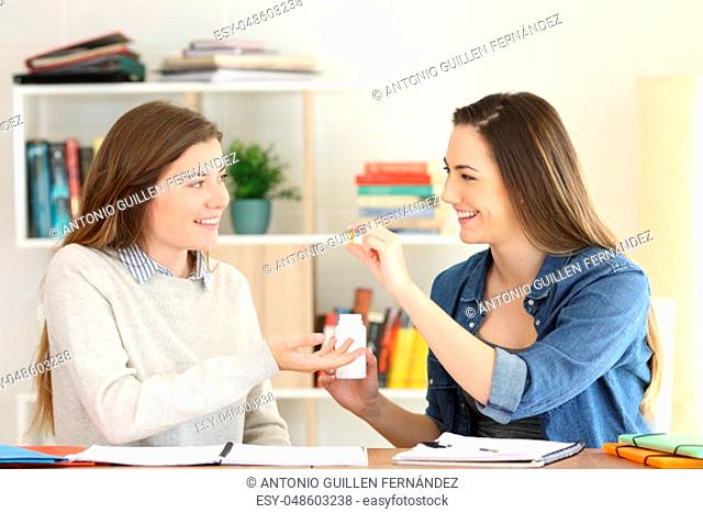 Student studying and offering a vitamin supplement to a friend at home