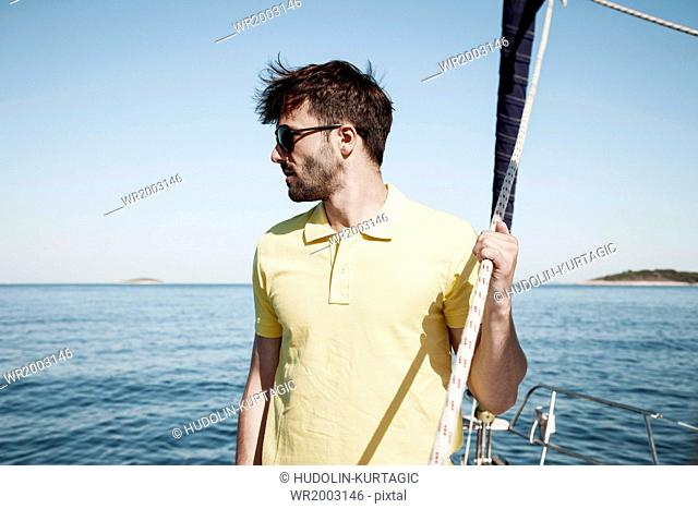 Young man overlooking sea on sailboat, Adriatic Sea