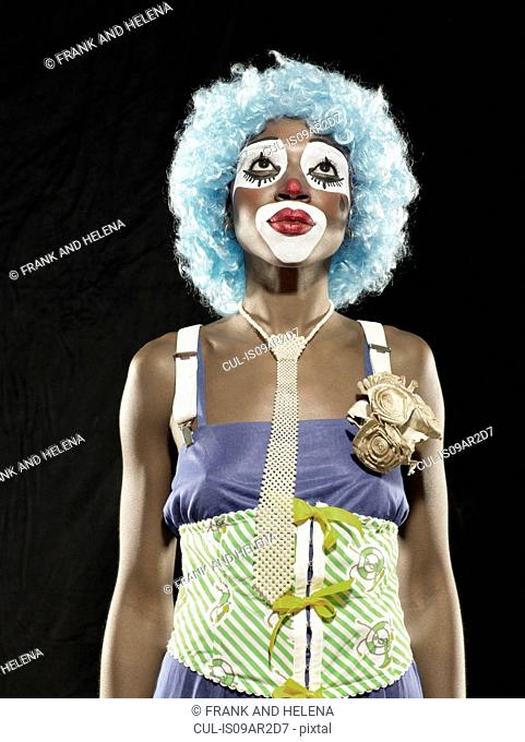 Studio portrait of young woman wearing clown face paint and blue wig looking up