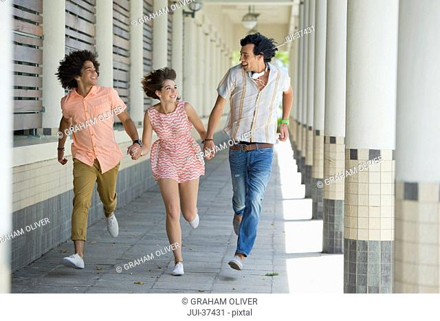 Enthusiastic friends holding hands and running along corridor