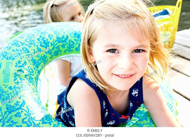Portrait of cute girl playing with inflatable ring on pier at lake Starnberg, Bavaria, Germany