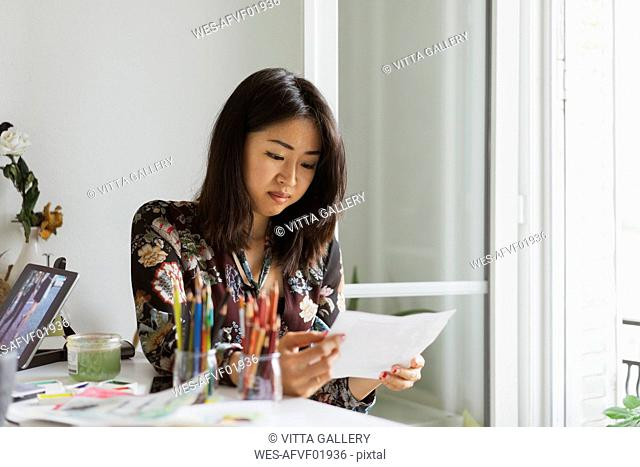 Content illustrator sitting at work desk in atelier looking at drawing