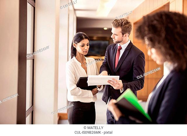 Young businesswoman and businessman reading paperwork in office corridor