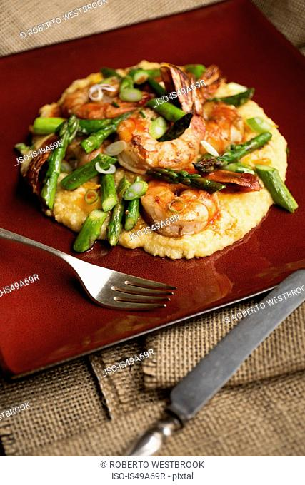 Shrimps and asparagus served on bed of polenta