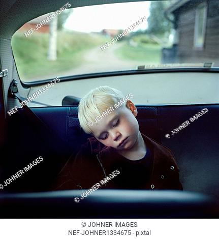 Boy sleeping on back seat of car