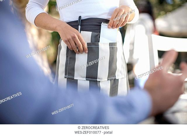 Waitress taking pen and notepad out of apron, partial view