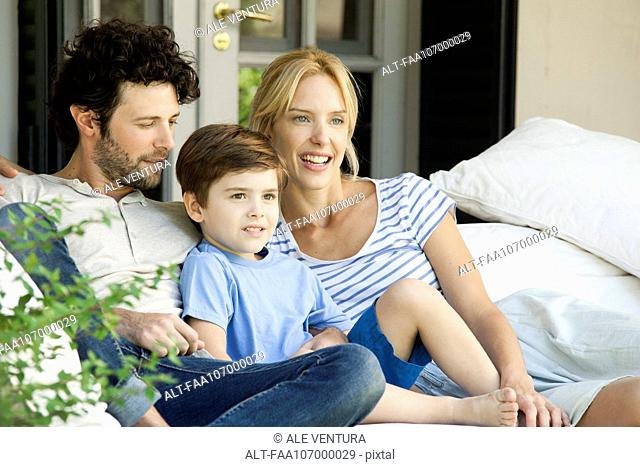 Family with one child relaxing together outdoors