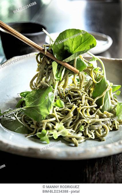 Chopsticks lifting soba salad noodles