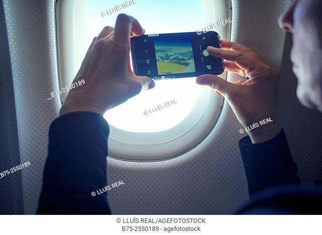 Closeup of hands of a young woman taking a picture with a mobile phone, -through a window in an airplane