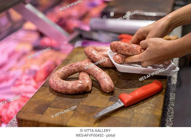 Female butcher cutting sausage
