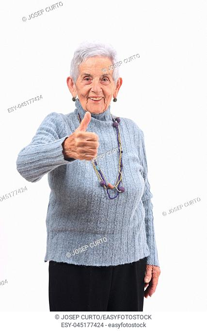portrait of senior woman with thumbs up on white
