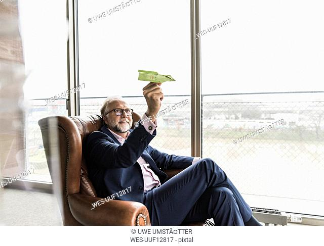 Smiling mature businessman sitting in leather armchair holding paper plane