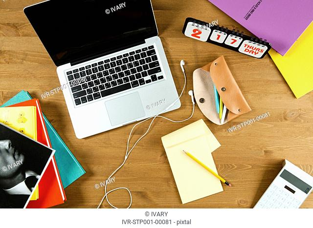 High Angle View Of The Laptop With Earphone, Notepad, Books