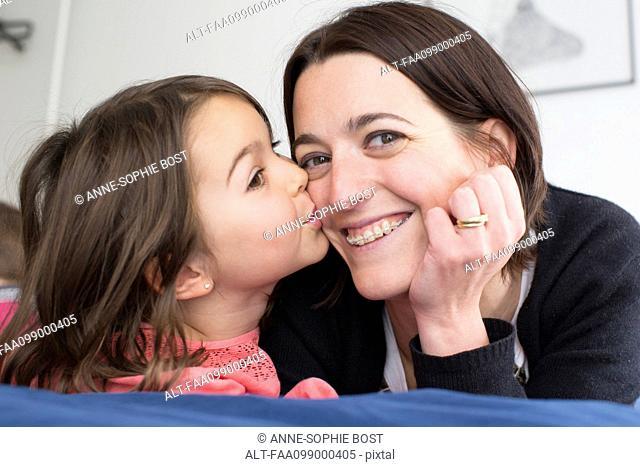 Little girl kissing mother's cheek