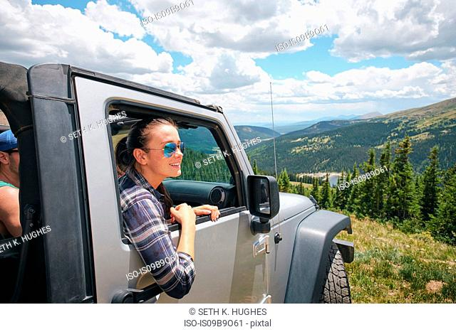 Young woman on road trip looking out from parked off road vehicle, Breckenridge, Colorado, USA