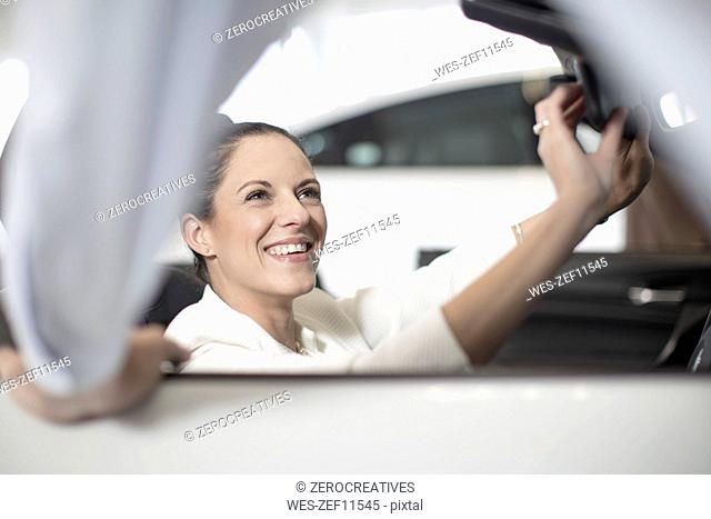 Smiling woman sitting in car at car dealership