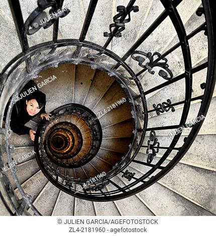 Asian woman in the spiral (helical) staircase in the tower of the Basilica of St Stephen. Hungary, Budapest, Pest, Belvaros. Model Released