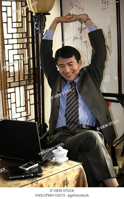 Chinese Business Man Using The Notebook PC