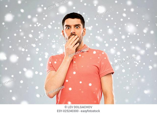 emotion, fear, winter, christmas and people concept - scared man in polo t-shirt over snow on gray background