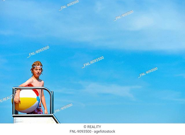 A boy holding a ball is standing on a slide in an open air bath