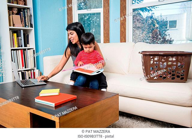 Woman using laptop while toddler son looking at notebook on sofa