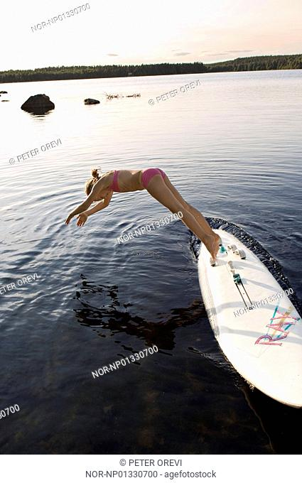 Woman diving off a surfboard into the sea, Sweden