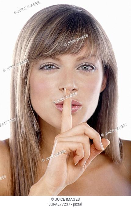 Woman putting her finger over her mouth
