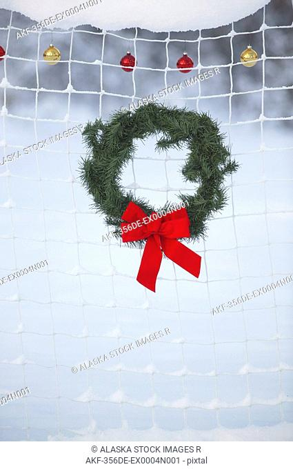 Holiday Wreath & Christmas Ornaments hanging on net in snow Mat-Su Valley Southcentral Alaska Winter