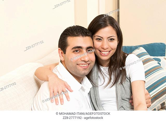 Happy couple sitting together on the sofa