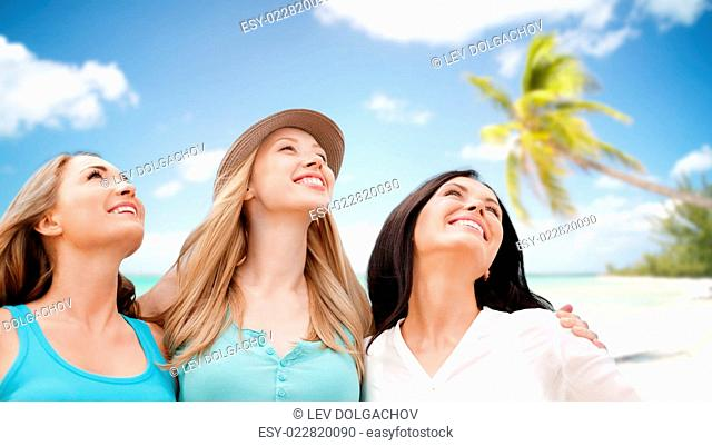 summer holidays, people, travel and vacation concept - group of smiling young women chilling over tropical beach background