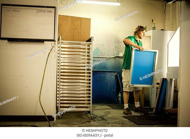 Man holding frame in screen print workshop
