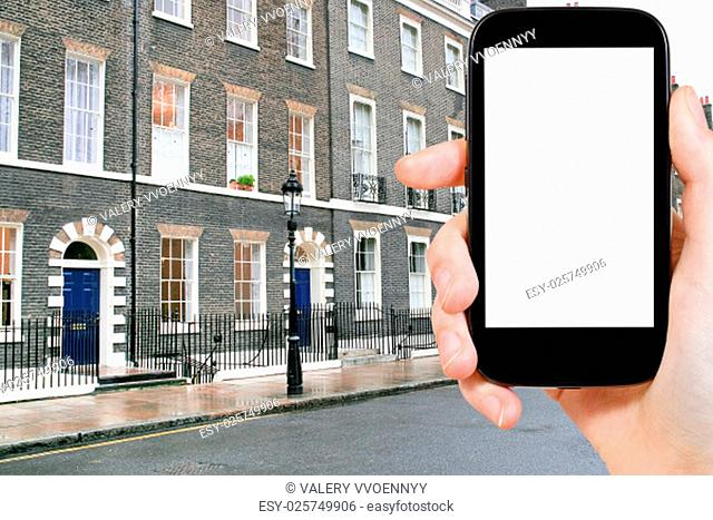 travel concept - hand holds smartphone with cut out screen and London apartment house on background