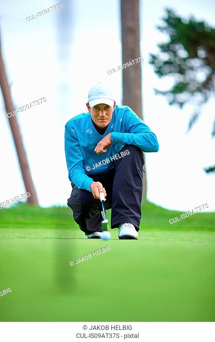 Front view of golfer crouching down considering strategy