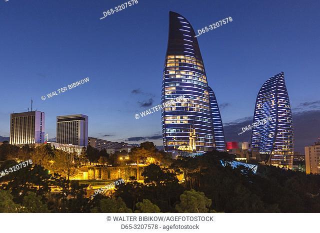 Azerbaijan, Baku, Flame Towers with mosque, dusk