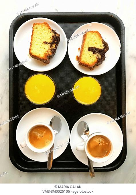 Two cups of coffee, two glasses of orange juice and two pieces of cake on a tray. View from above