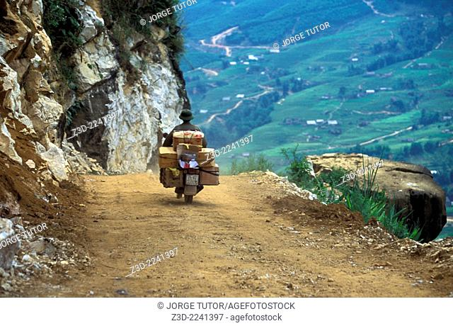 Motorbiker full of parcels in an unpaved Sapa to Ta Van road Vietnam