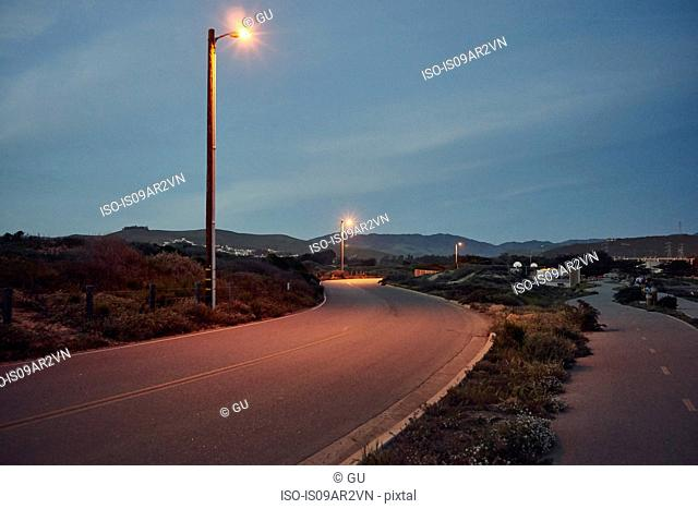 View of street lights on winding road at dusk