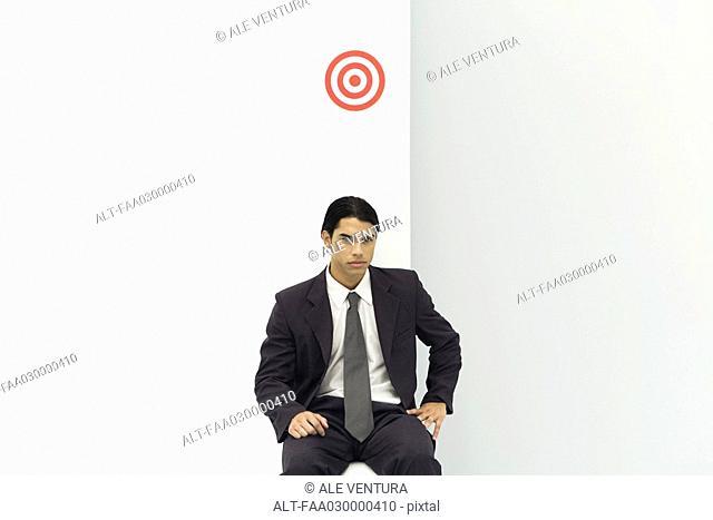 Young businessman sitting below bullseye, looking at camera