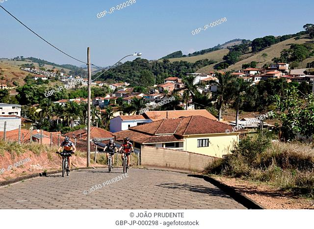 Cyclists cycling on city streets are part of the route of the Path of Faith that links the cities of Águas da Prata to Aparecida, Tocos do Moji, Minas Gerais