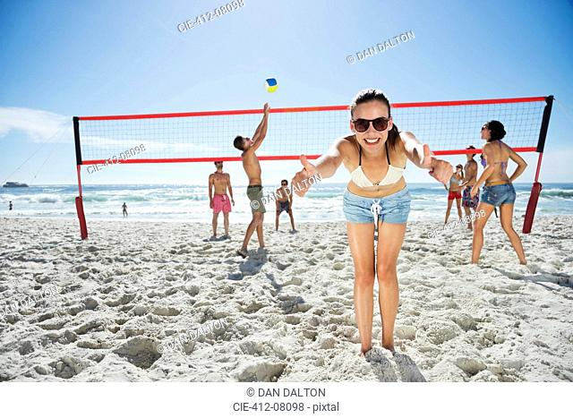 Portrait of confident woman gesturing thumbs up on beach volleyball court