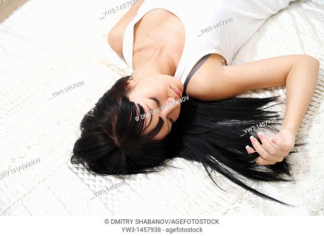 pretty brunette girl lying on the bed indoors