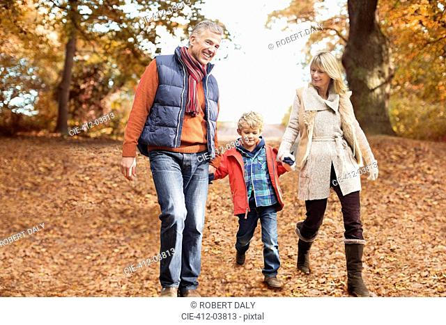 Older couple walking with grandson in park
