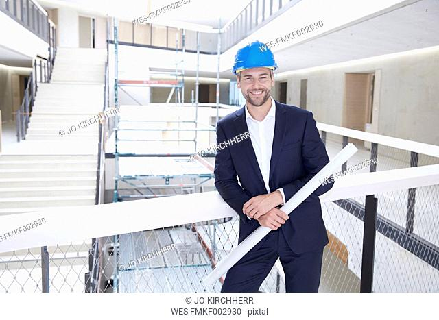 Smiling architect in office building wearing hard hat