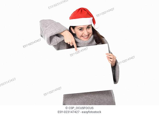 young sweet Latin woman in Santa Christmas hat pointing blank billboard