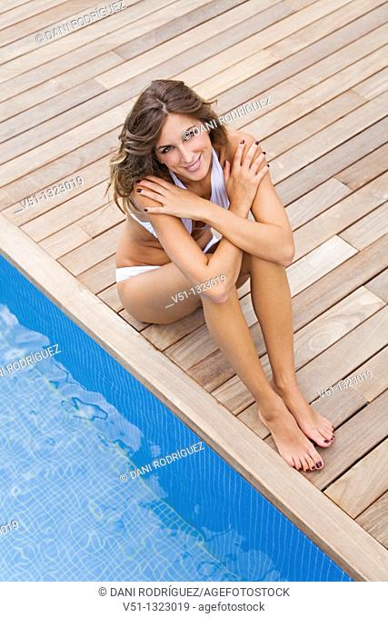 Portrait of a blonde woman sitting by the pool and smiling at camera