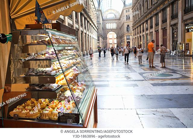 View on Naples Gallery with sweets in foreground, people walking around. Galleria Umberto I, Naples, Italy