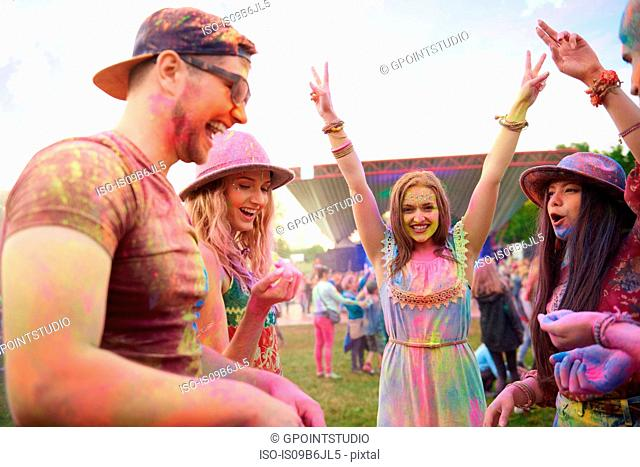 Young adult friends dancing covered in coloured chalk powder at festival