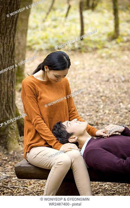 Young smiling couple having a date on bench in forest in fall face to face