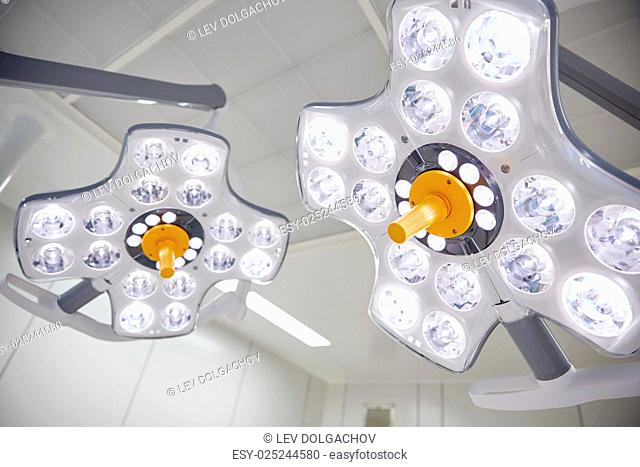 medicine, surgery and equipment concept - surgical lamps in operation room at hospital