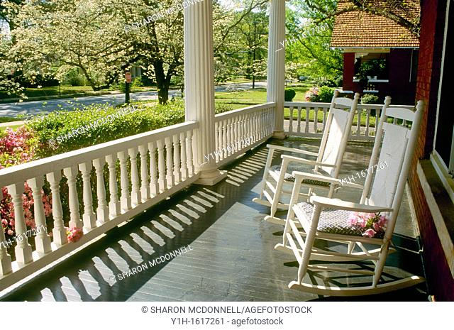 Two rocking chairs sit on wide front porch looking out over spring street blooming with dogwood, azaleas, and pears, Georgia, USA